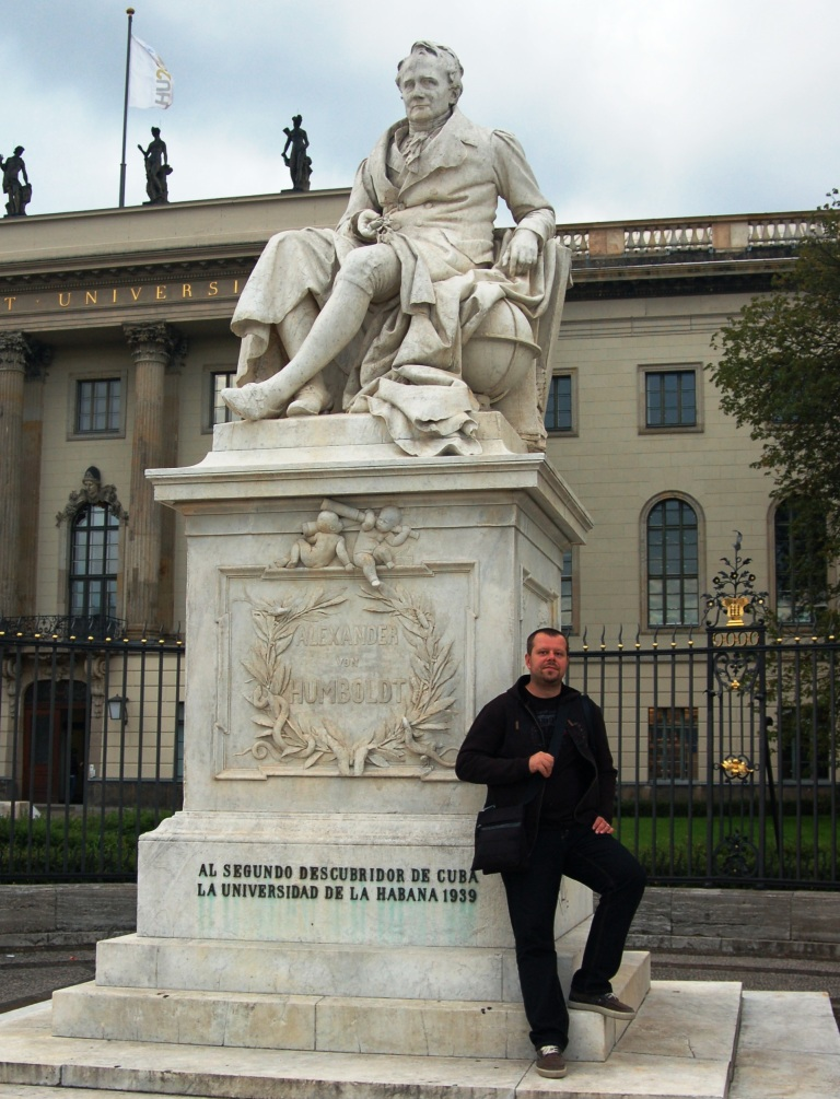 Young man student in front of Humboldt statue, Humboldt University, Berlin Germany